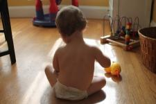 Silhouette of a baby. The baby's back is turned away from the camera, facing a window with sunlight. A rubber duck and several other toys are placed on the baby's side.