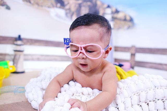 "A baby plays with a blanket that they are laying on. The baby is wearing pink glasses frames without lenses, with the words ""Kiss."""