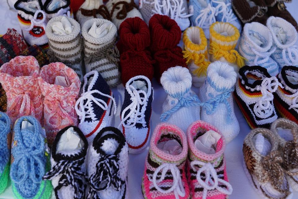 Rows of colorful crochet baby booties.