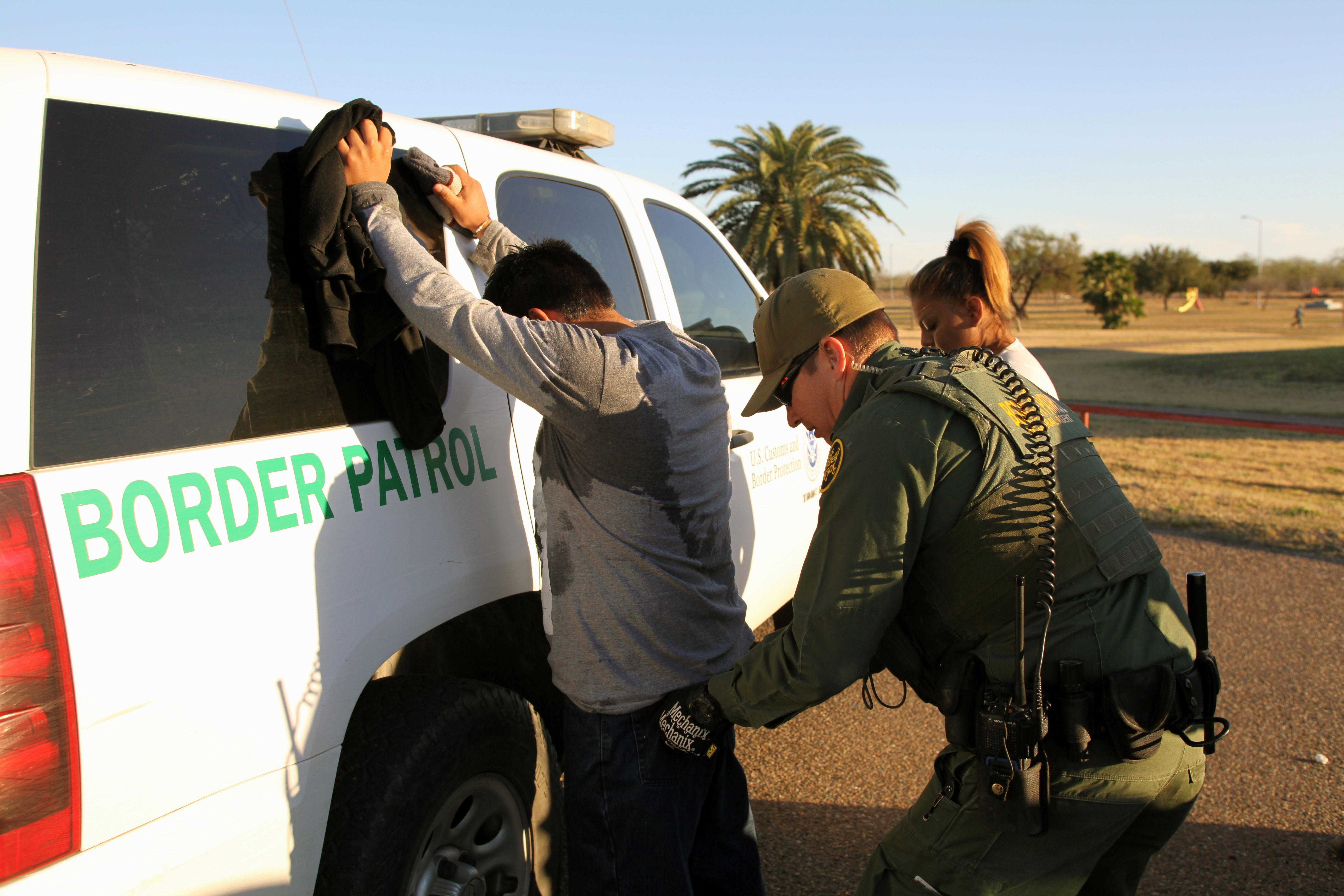 A Border Patrol agent takes a man into custody