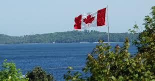 The Canadian flag (Red, White, and the another Red strip with a red maple leaf in the middle of the white section of flag) waving in the trees in front of a large body of water.
