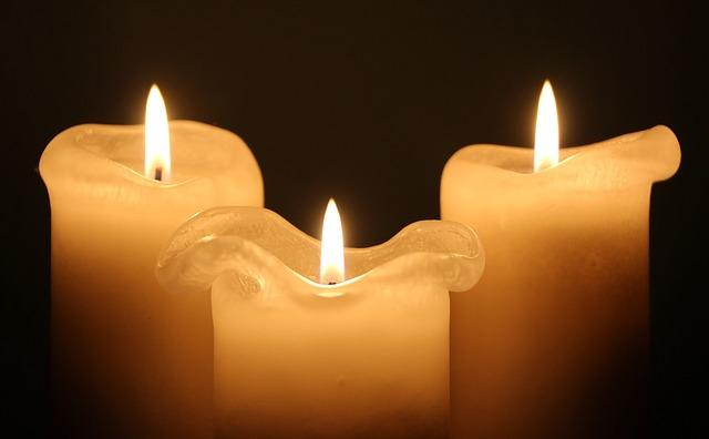 Three burning white candles, in a dark room. Candle wax drips on each.