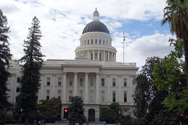 Landscape photo of the CA Capitol Building, against a blue sky and surrounded by trees,\.