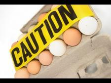A filled egg carton is opened. Caution tape is placed across.