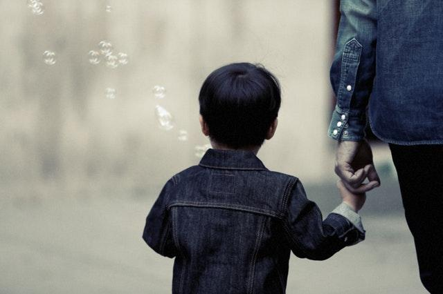 The back of a child walking with an adult who is holding their hand. Surrounding the child are bubbles in the wind.