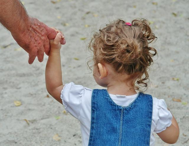 A small child with curly hair holds a finger on an adult's hand