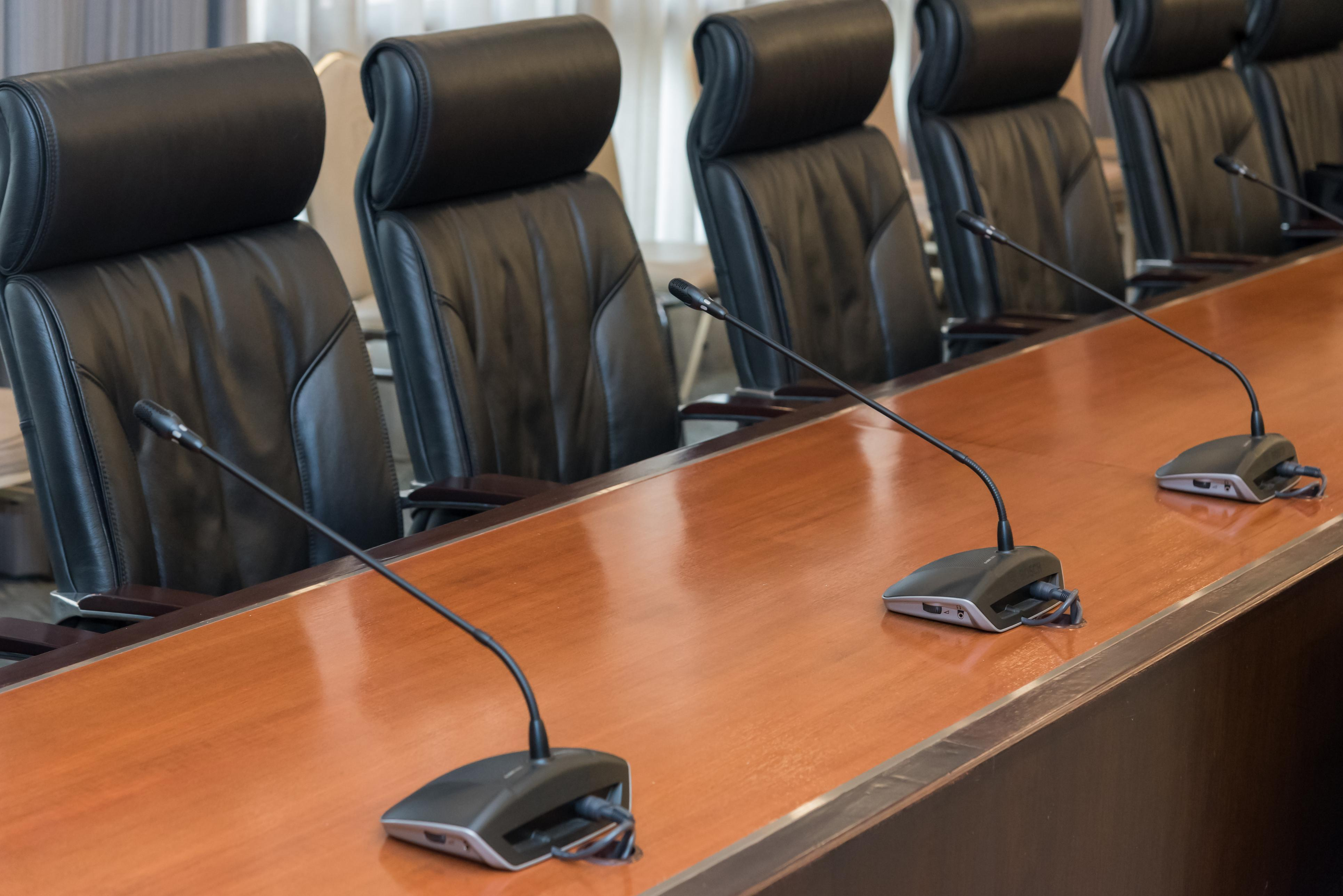 Empty chairs at a board room table with microphones