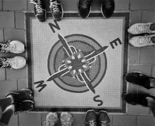 Black and white image of the compass directions--North, East, South and West-- on the ground, with humans wearing shoes surrounding it.