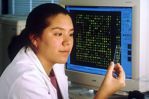 Female laboratory technician sitting at computer that displays a DNA microarray