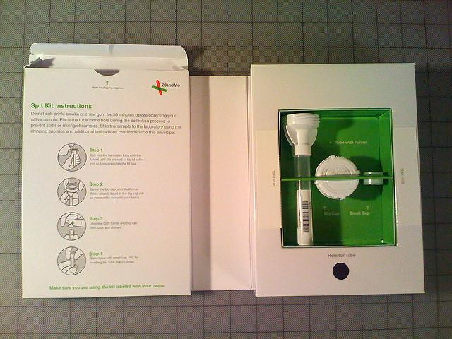 the contents of a 23 and Me test kit: test tube with funnel and two white caps in a white and green box