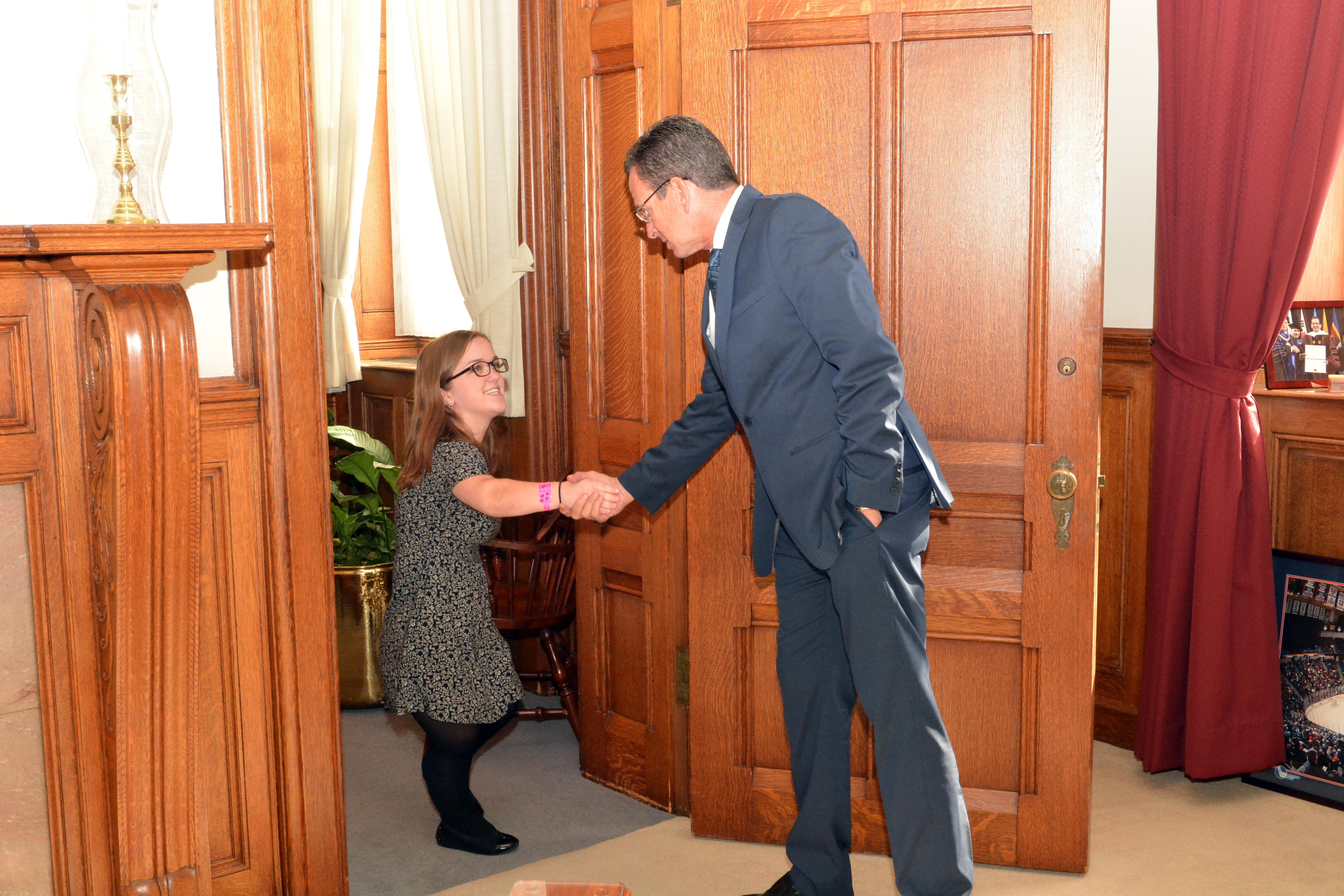 a little person shakes hands with a politician