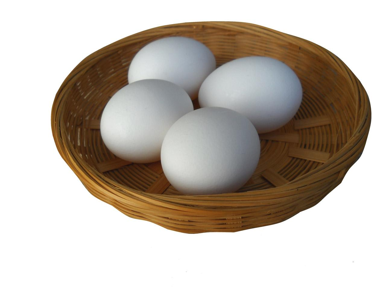 Four eggs in a shallow wicker basket