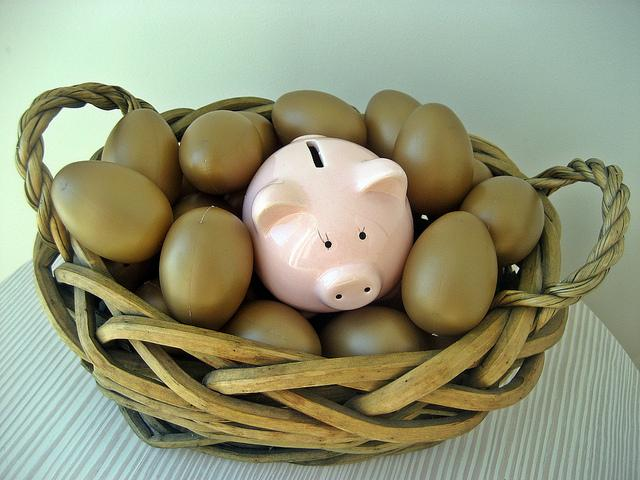 A small, pink ceramic piggy bank is nestled in the middle of a woven basket full of golden eggs.