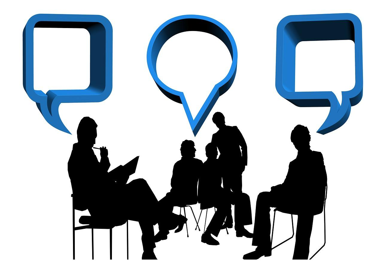 Silhouettes of 4 people sitting in chairs. Word bubbles suggest that they are exchanging ideas.