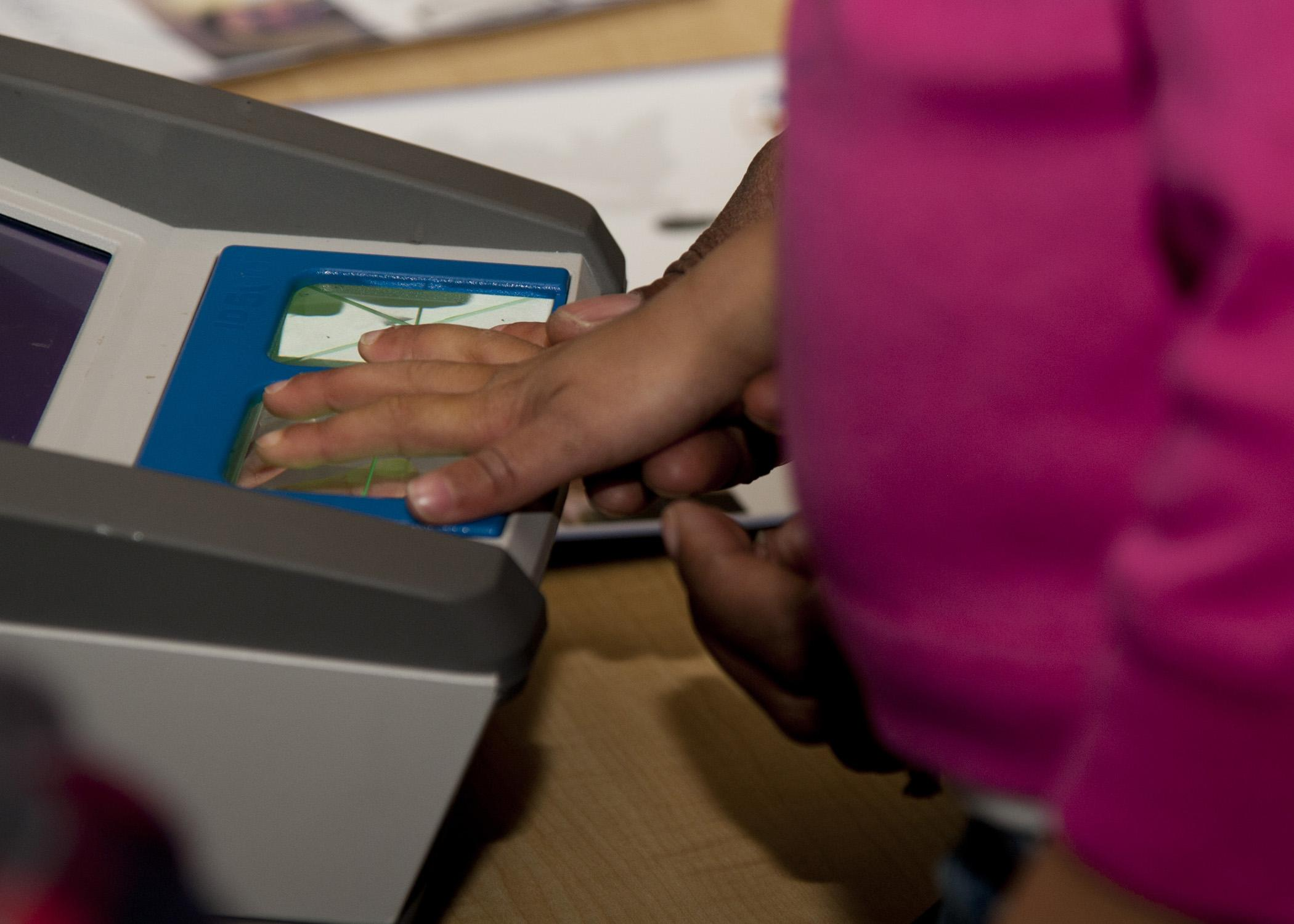 An individual's hand is held to a scanning machine for fingerprinting.