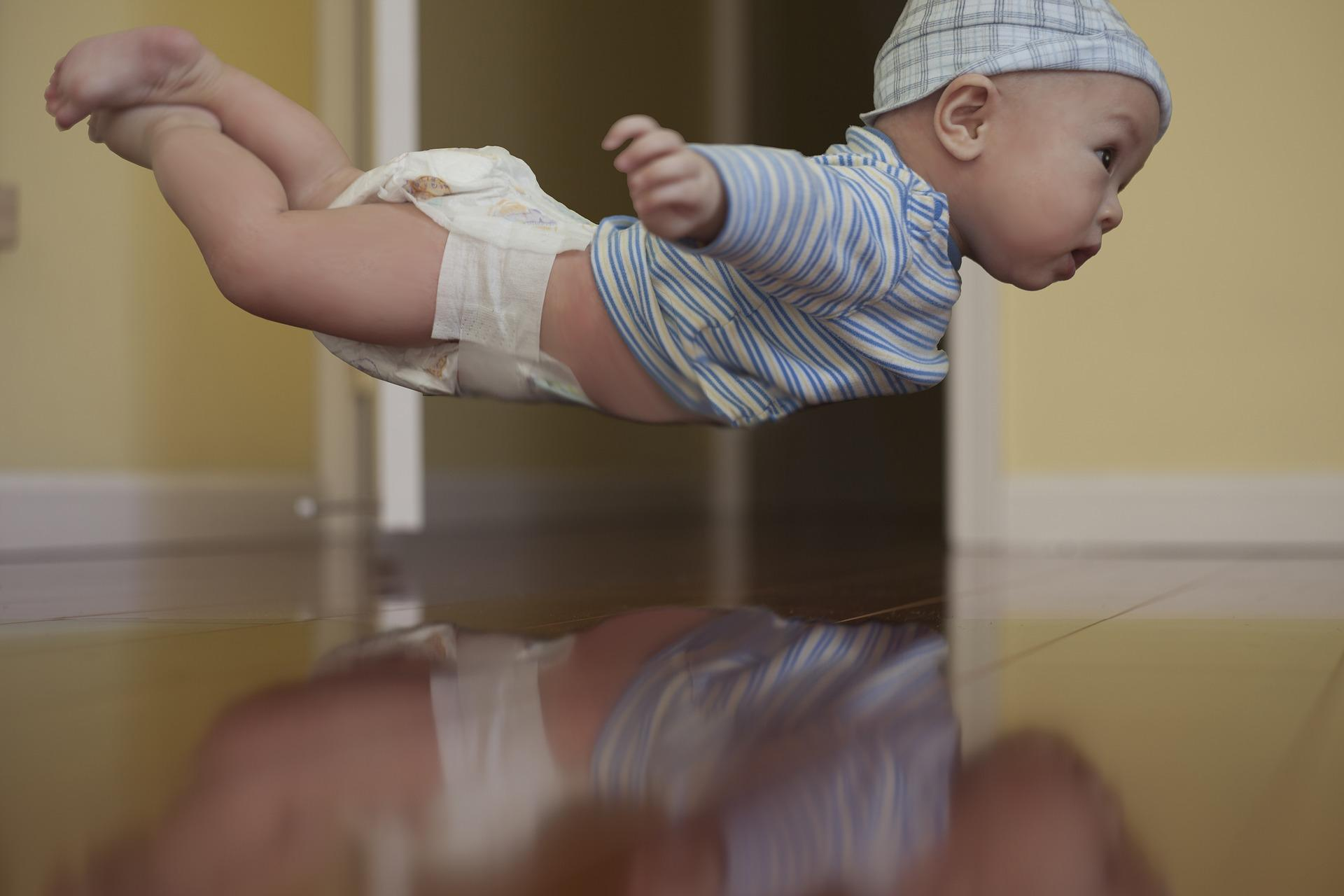A baby dressed in a shirt, diapers, and cap, floats mid-air.