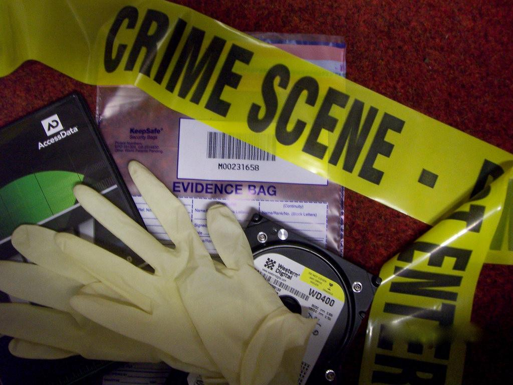 Forensic materials on a red background--gloves, crime scene tape, and evidence bags