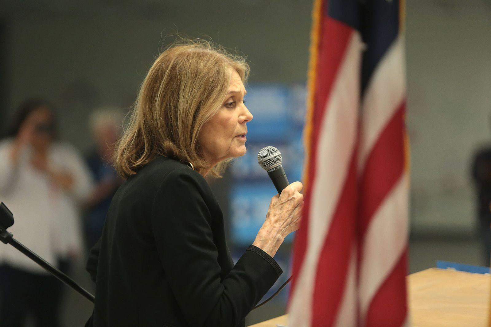 Gloria Steinem speaking in front of an American flag