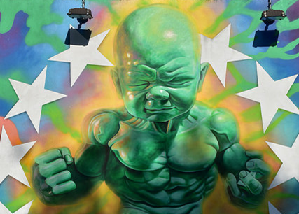 Street art depiction of a large, green baby with muscular chest and arms, surrounded by a semicircle of white stars against a multicolored background