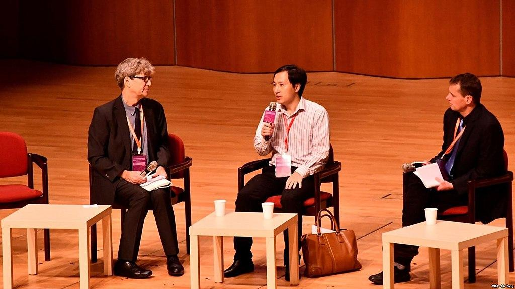 He Jiankui sitting and speaking into a microphone with a panel of speakers