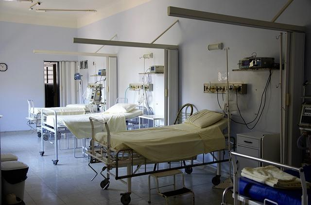 Three empty hospital beds are shown in a dimly lit room.