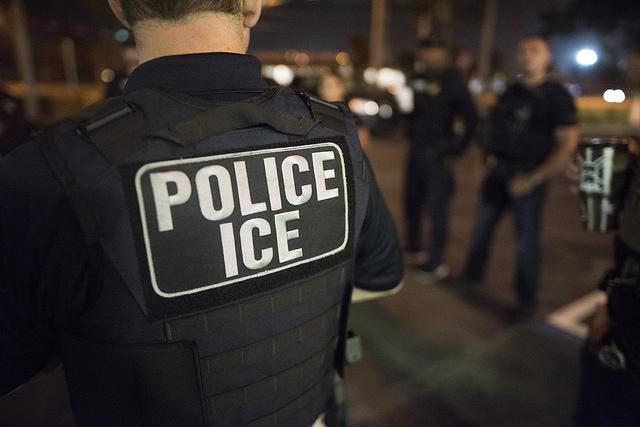 "An image of an ICE officer facing away from the camera. The uniform okn the officer's back reads ""POLICE / ICE."""