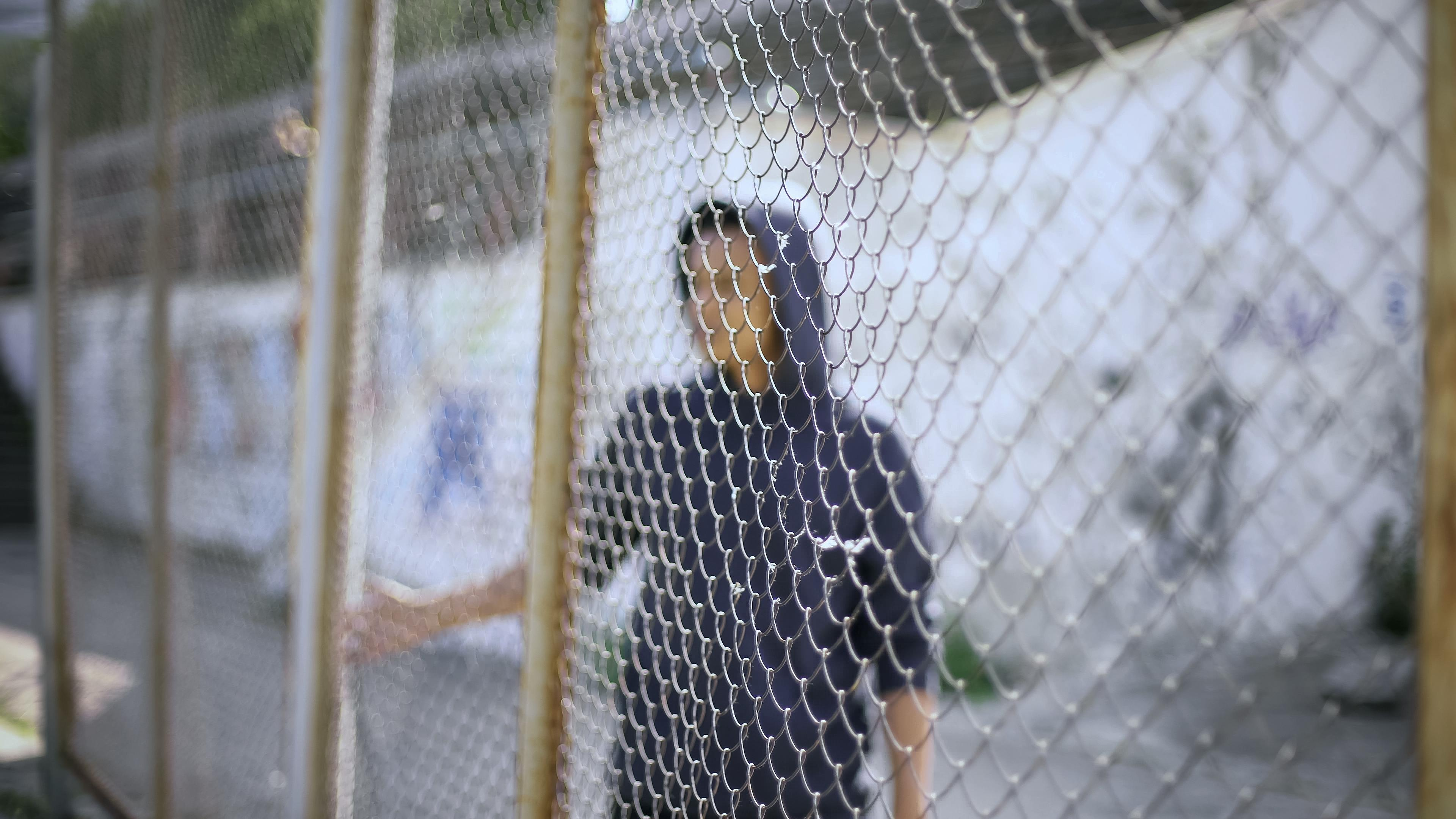 a boy in a blue hoodie stands behind a cyclone fence