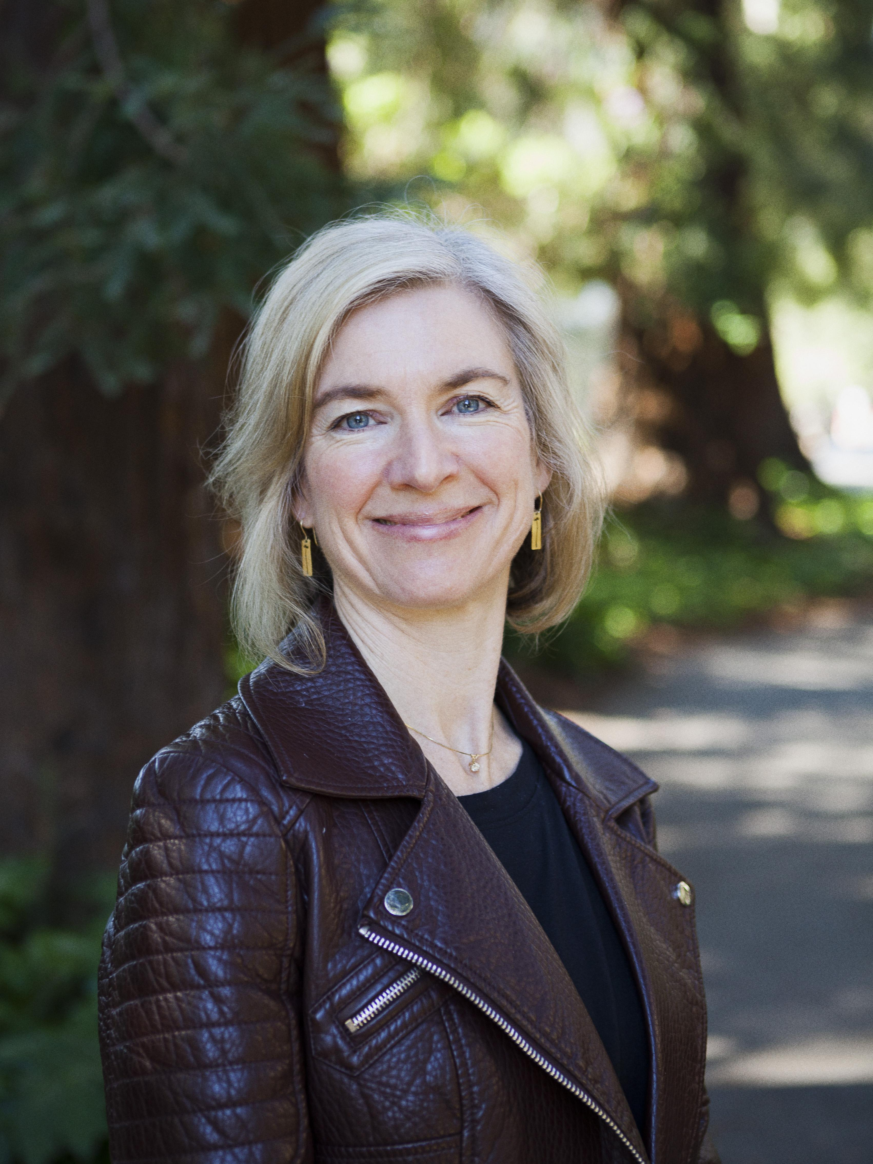 Portrait photo of Jennifer Doudna casually dressed and smiling in front of shaded trees.