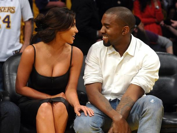 In the front row of a basketball game, Kim Kardashian and Kanye West look at each other, engaged in an amusing conversation