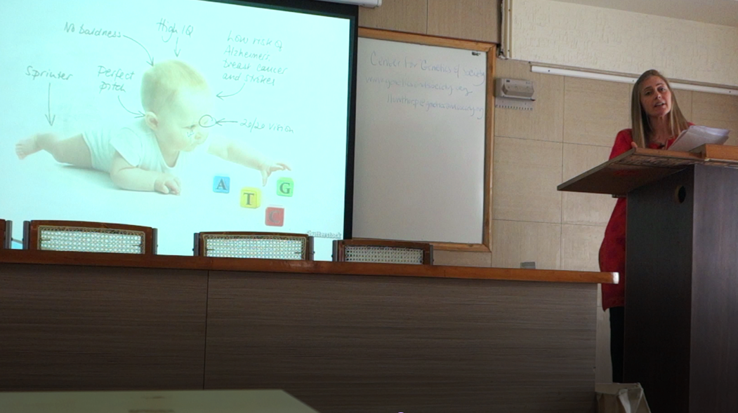 Tall blonde woman in Indian dress giving talk in front of an auditorium with a slide showing a designer baby