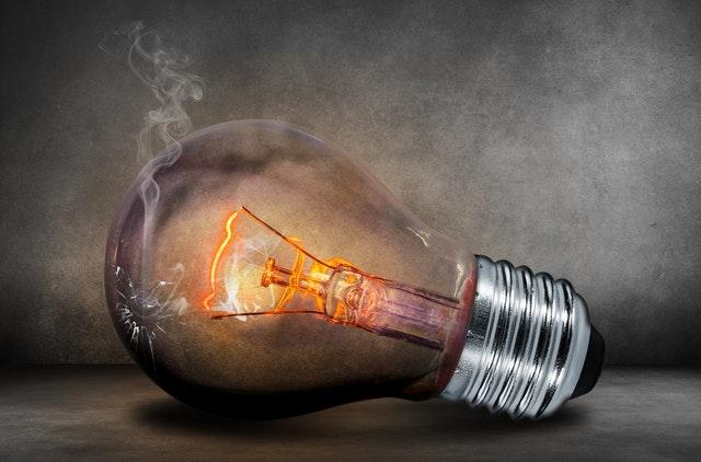 A cracked light bulb is tipped on its side,a weak current is visible causing a glow. The background has an eerie mix of black and white colors and shadow.