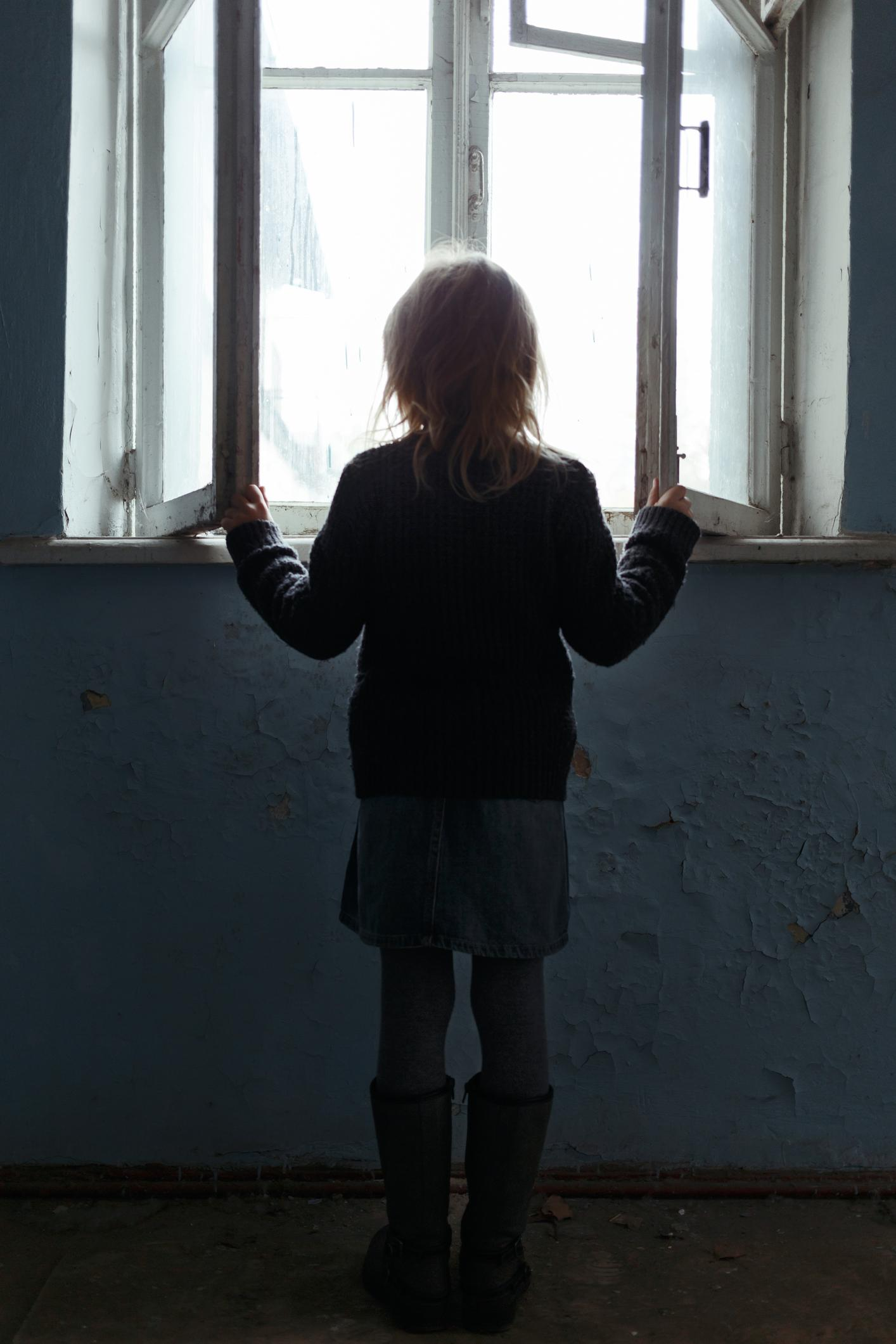 young girl stands in front of a window with back to camera