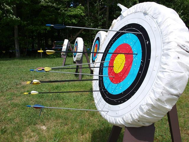 In the foreground, an archery target with several arrows scattered around the target. A line of targets are set up on the grass behind it.