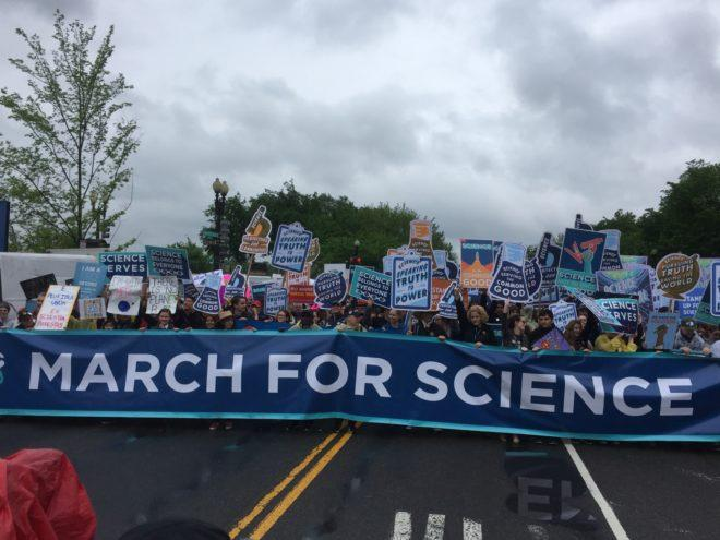 "Several protesters hold signs behind a long banner stating ""March for Science."""