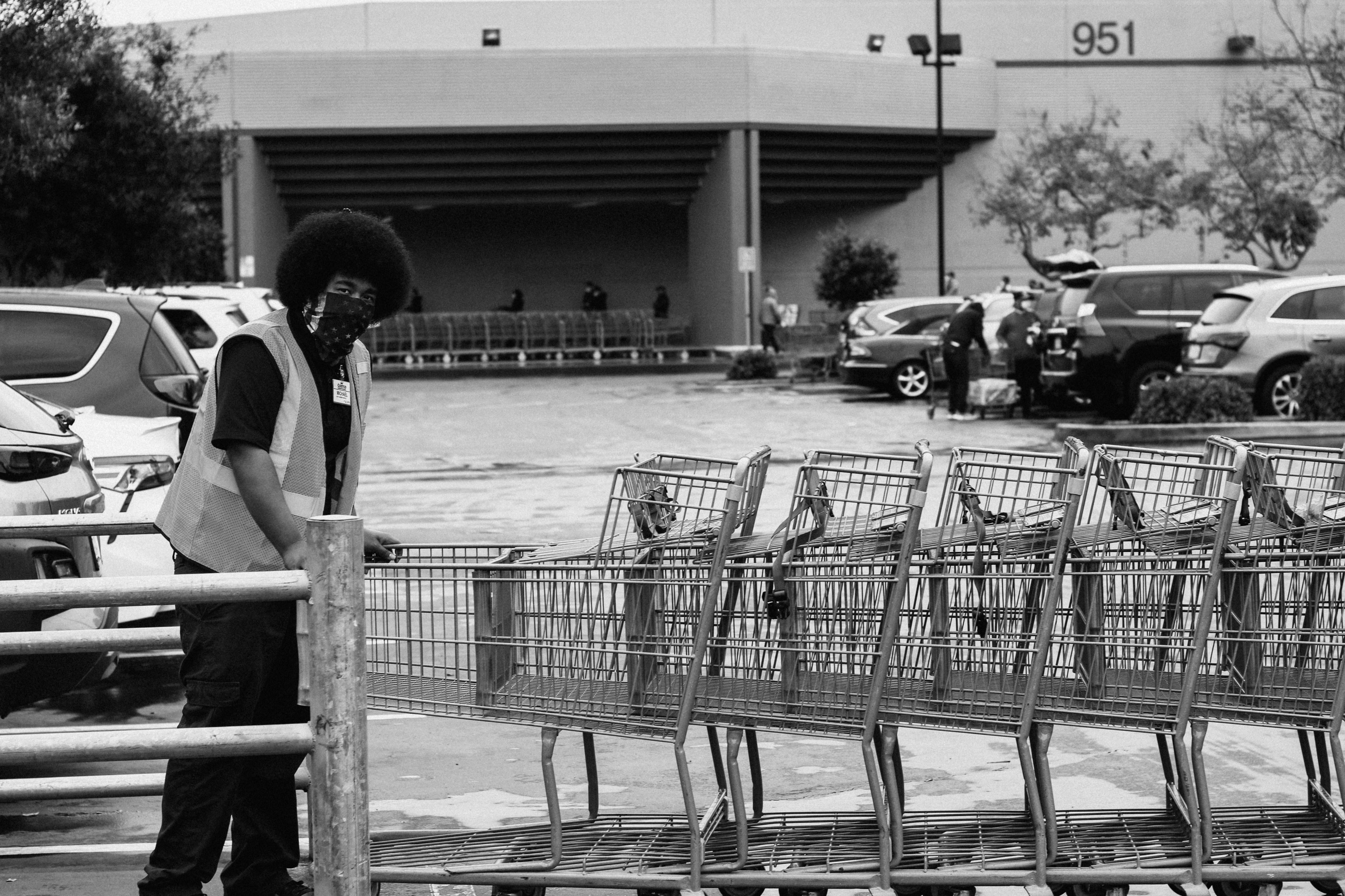 A black man, wearing safety vest and mask made from a bandana, pushes a line of grocery carts in a parking lot