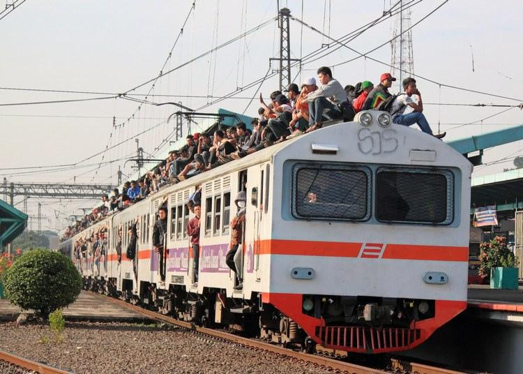 Men crowded into and on a train in India