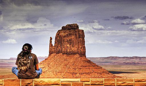 A young girl has ber back turned away from the camera, and sits on a rock, with jeans a brown t-shirt, and long hair. She looks onward to a rock and landscape.