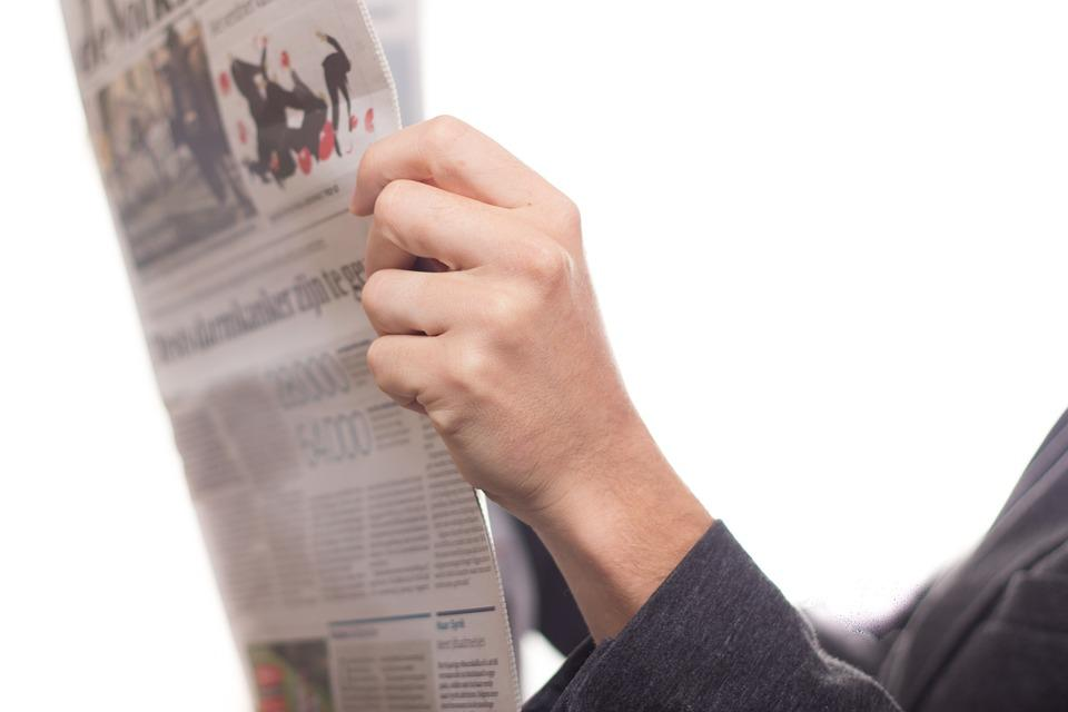 An image of someone holding a newspaper.