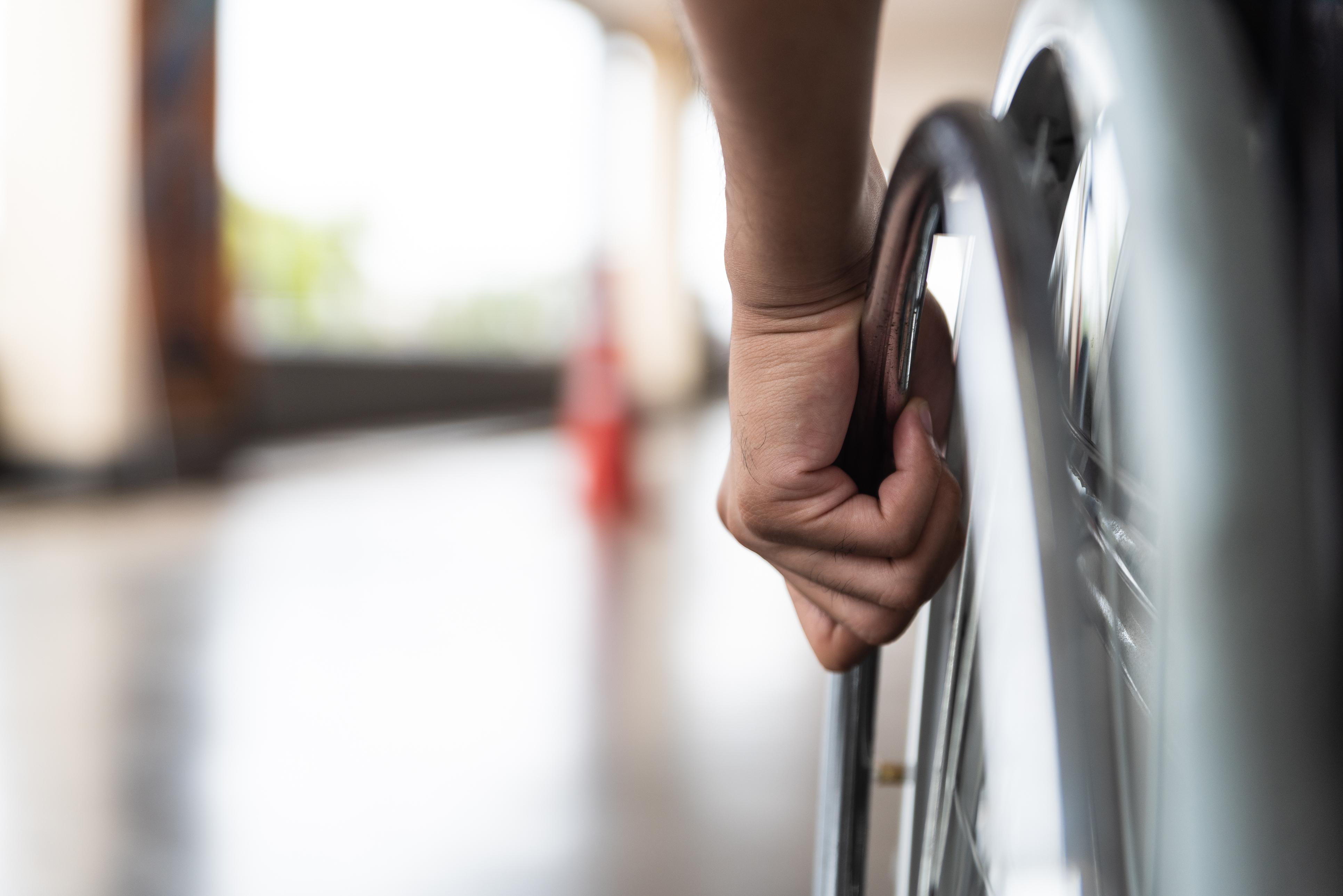 close-up image of a hand on a wheelchair wheel