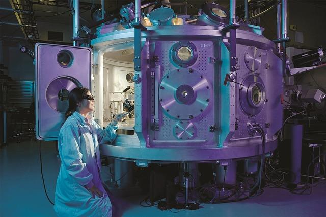A person dressed in a lba coat looks through a large chamber