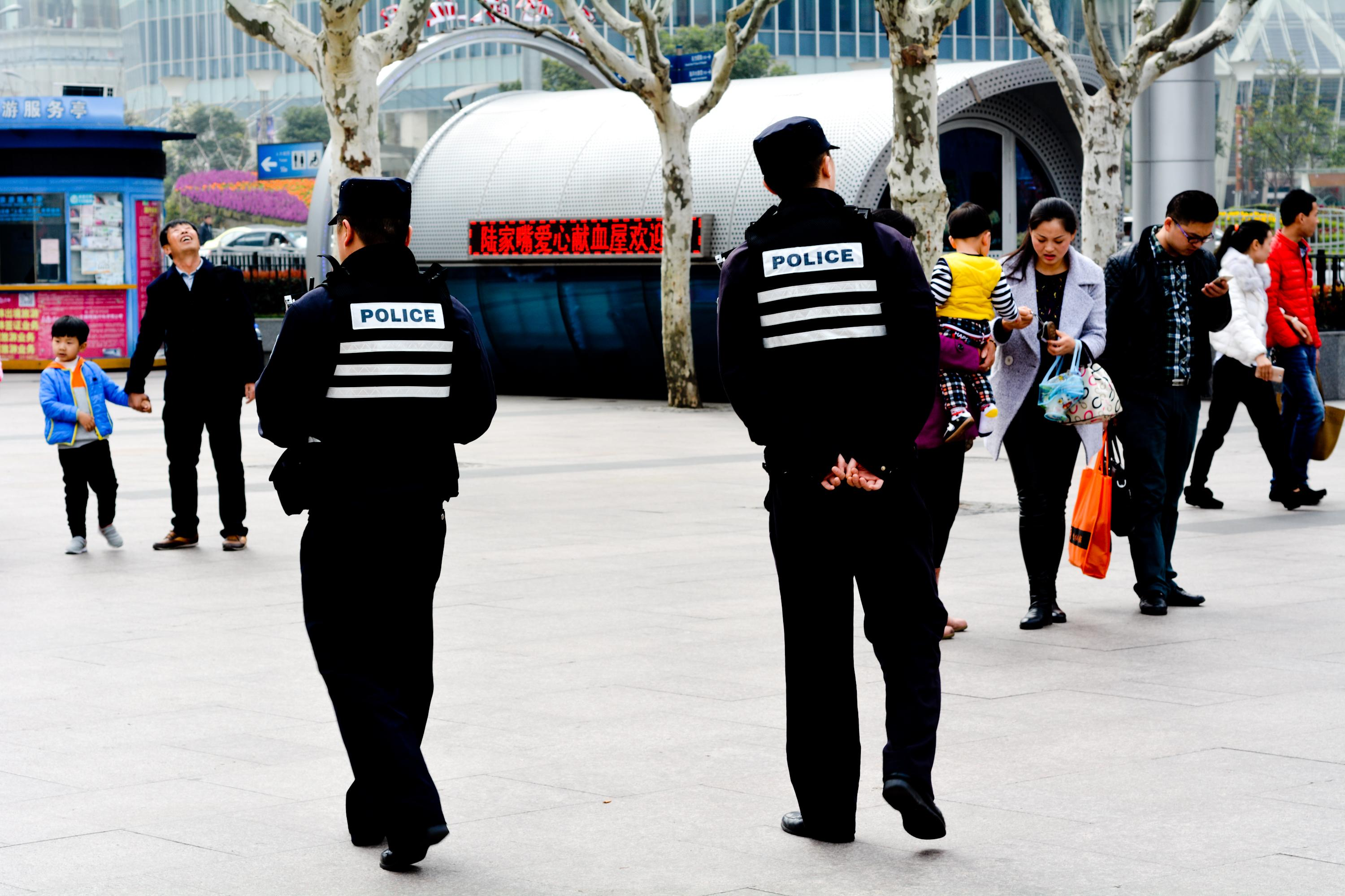 Two police officers in China patrol a city square