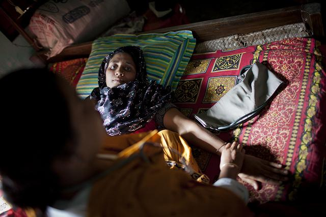A pregnant woman lays on a bed of blankets with her arm extended, as another woman with medical tools touches her arm.
