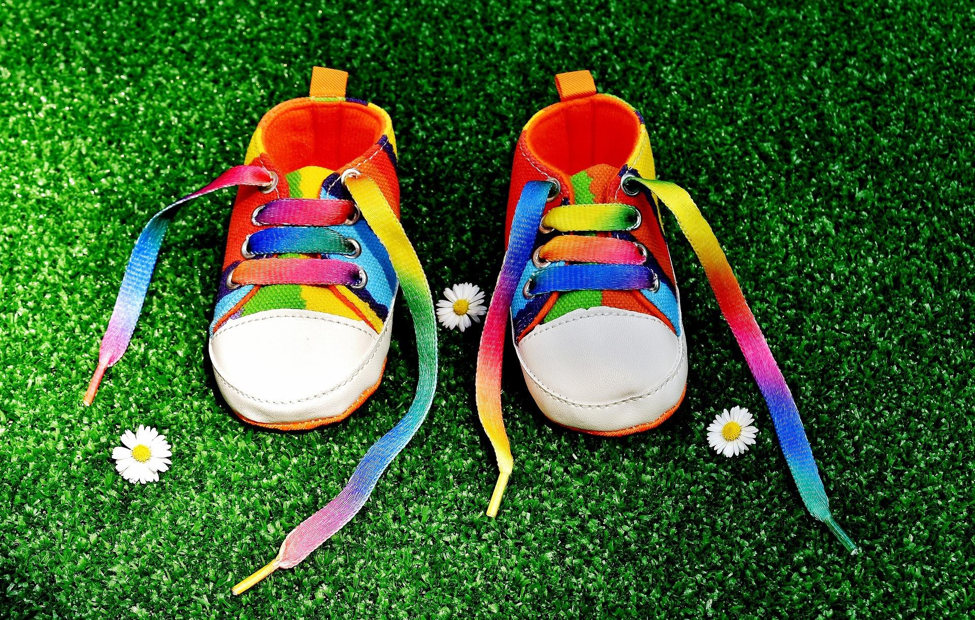Rainbow colored baby shoes on bright green grass with a few daisies