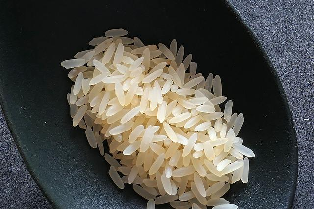 Uncooked white rice in a circular bowl container.