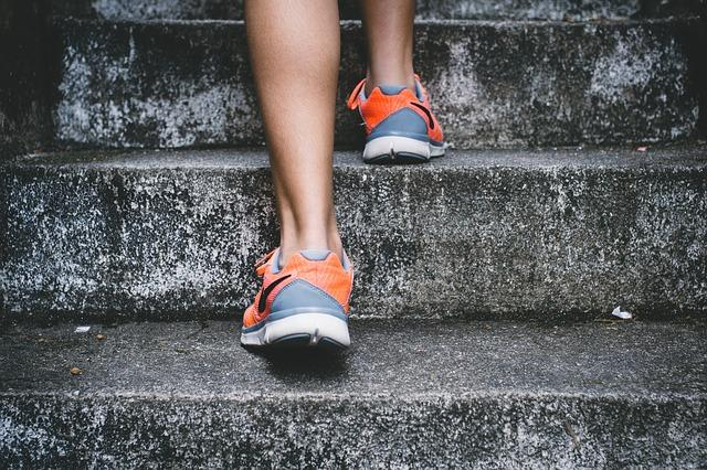 Close up of a runner, running up cement stairs.