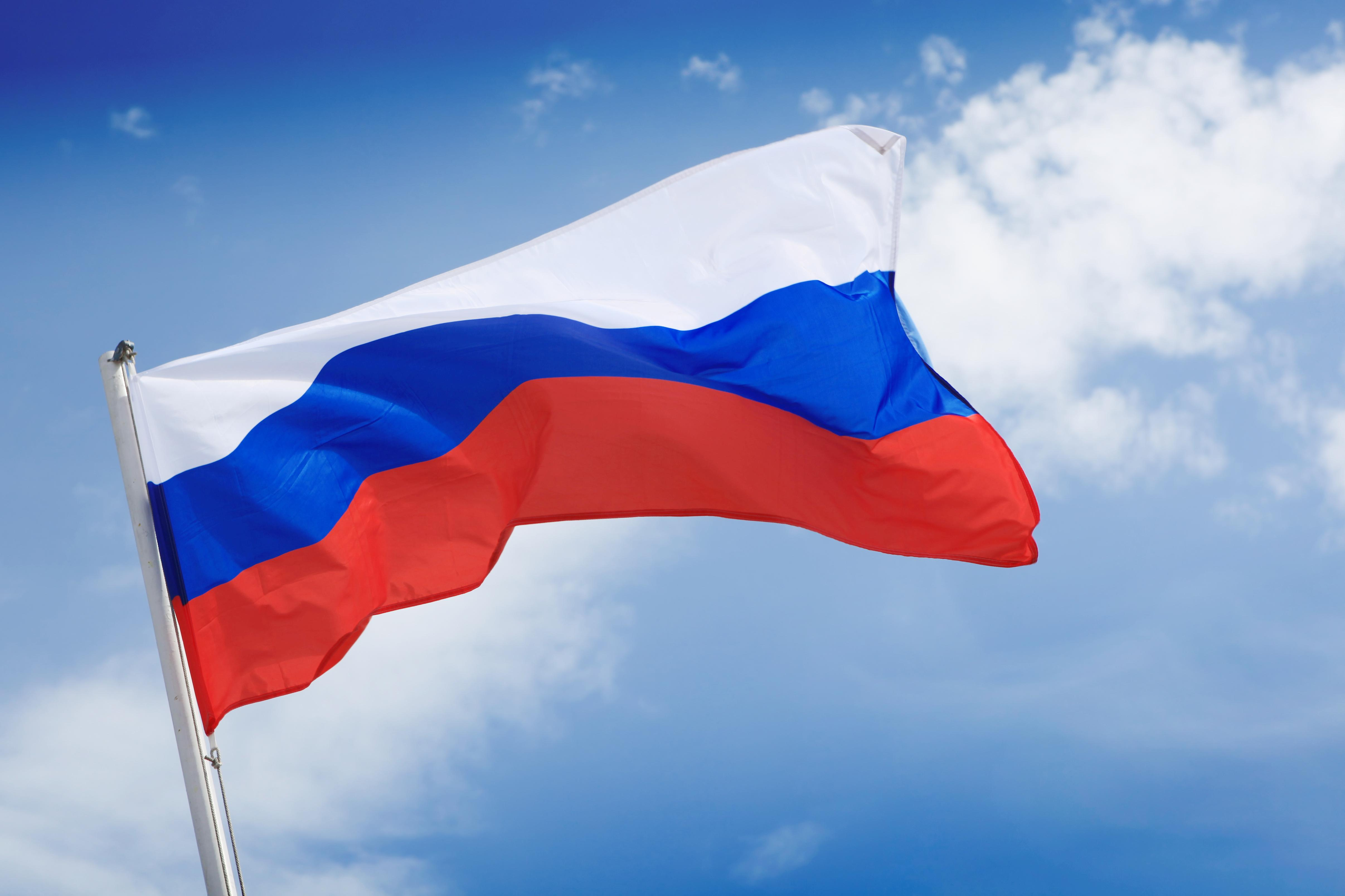 Photo of the Russian flag and a blue sky with clouds
