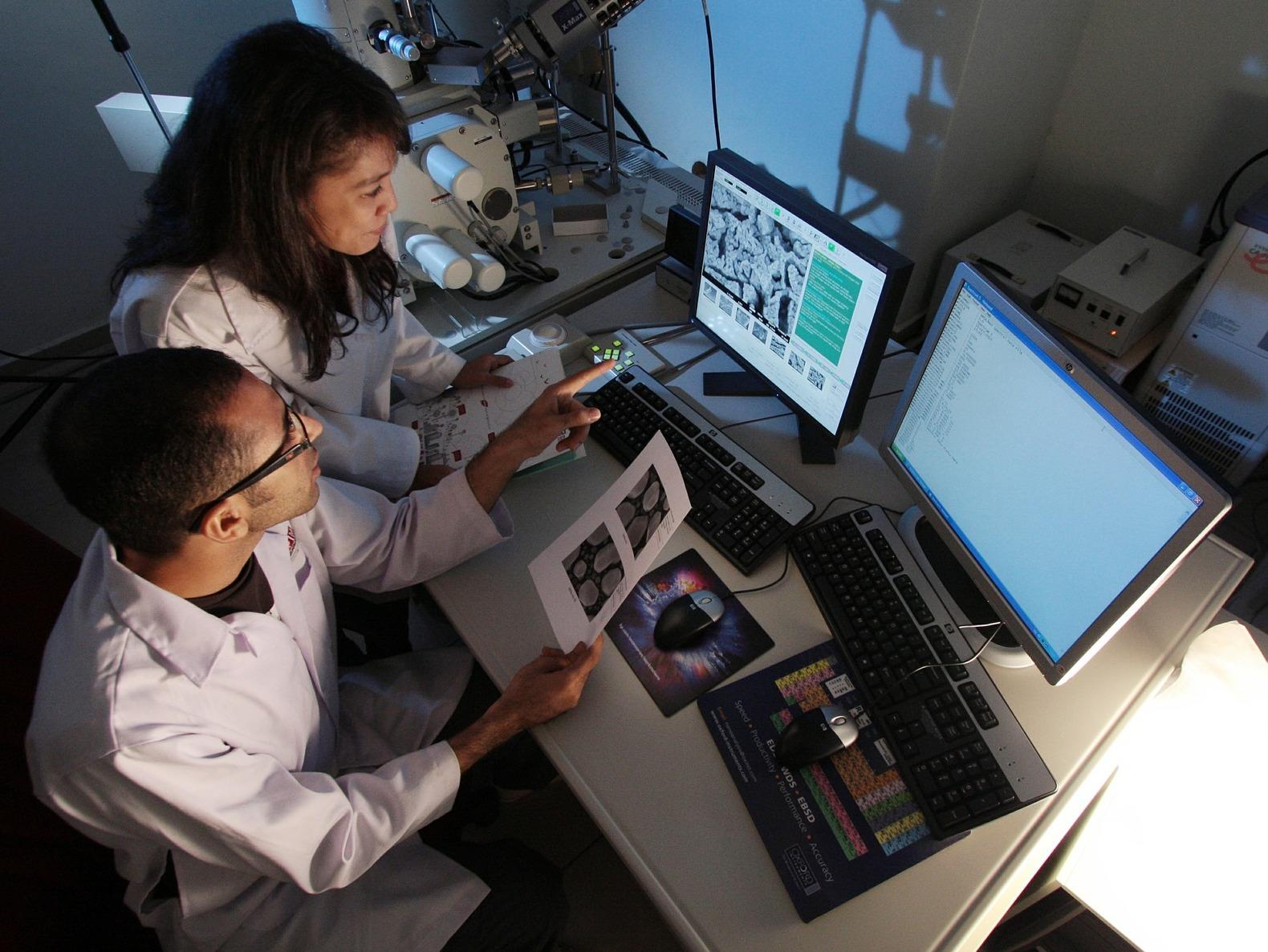 A female and male scientist sitting in a dark lab in front of a screen analyzing images of cells