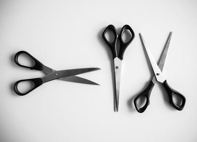 Bird's eye view of three scissors that look the same, lined up on a white table. The two on the sides are slightly opened, while the middle is completely closed.