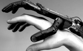A black and white image of a robotic hand lightly grasping a human hand.
