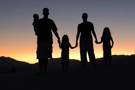 A shadow of a family of 5 holding hands in front of a sunset. Two parents, two toddlers, and a baby.